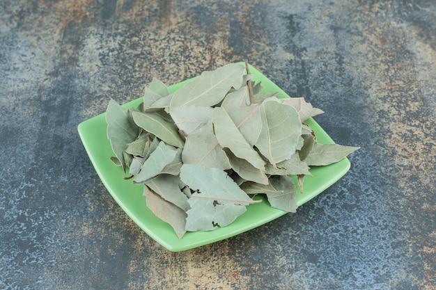 Grüne teeblätter auf grüner platte.