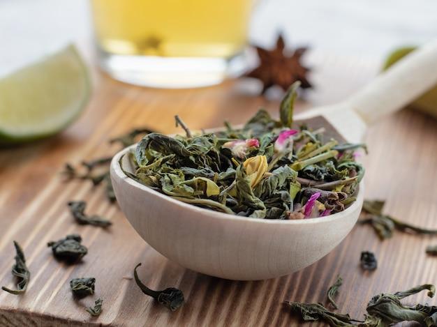 Grüne teeblätter im holzlöffel mit limettenscheiben auf hölzernem hintergrund oder oberfläche, nahaufnahme