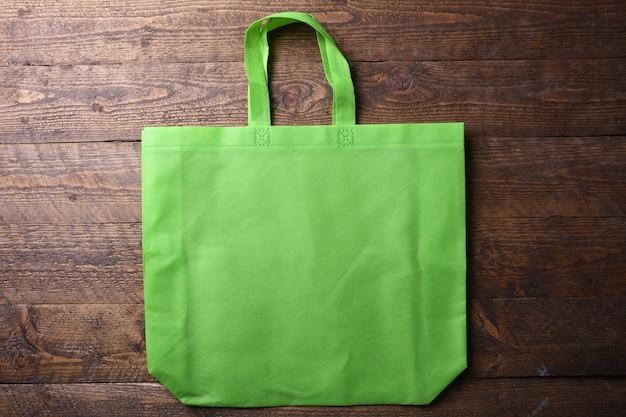 Grüne textiltasche auf hölzernem hintergrund