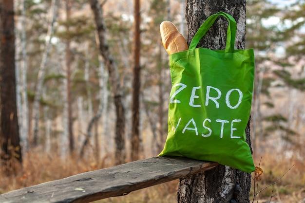 Grüne textiltasche mit der aufschrift zero waste auf dem hintergrund der natur mit französischem brot in der tasche