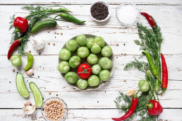 Grüne tomaten, essiggurken auf weißem holztisch mit den grünen und roten und paprikapfeffern, fenchel, salz, schwarze pfefferkörner, knoblauch, erbse, abschluss oben, gesundes konzept, draufsicht, flache lage