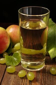 Grüne traube mit äpfeln und glas frischem fruchtsaft auf tisch auf grünem hintergrund.
