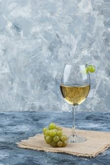 Grüne trauben der seitenansicht mit einem glas wein auf schmutz und stück sackhintergrund. vertikal