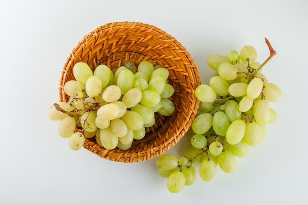 Grüne trauben in einem weidenkorb auf einem weiß.