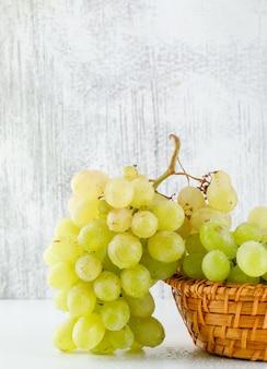 Grüne trauben in einem weidenkorb auf weißer und schmuddeliger nahaufnahme.