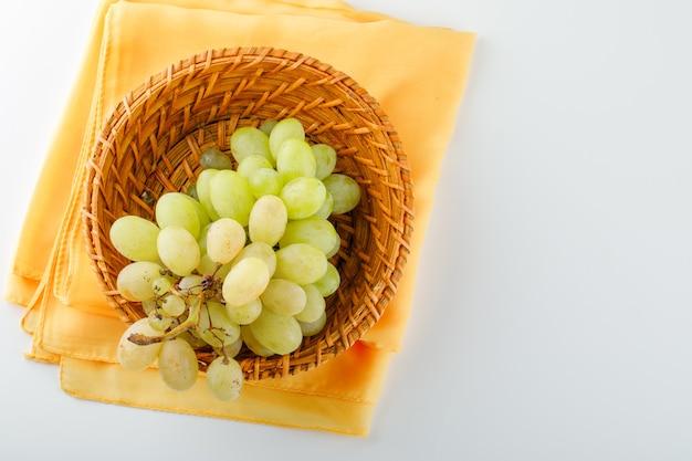 Grüne trauben in einem weidenkorb lagen flach auf weiß und textil