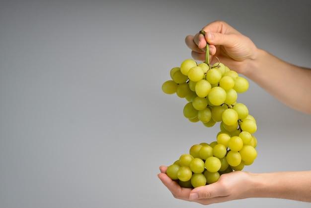 Grüne trauben in weiblichen händen gesunde ernährung, vegetarisches ernährungskonzept