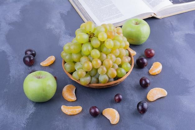 Grüne trauben mit apfel, mandarine und kirschen.