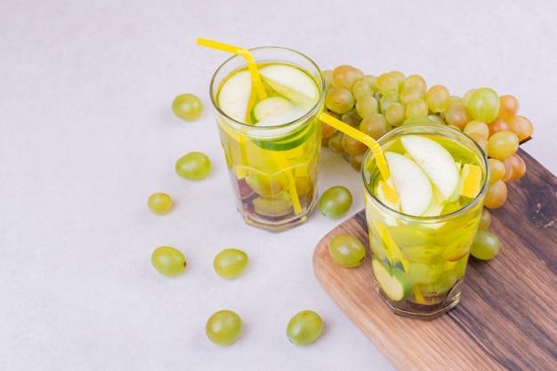 Grüne trauben mit zwei gläsern saft auf einem holzbrett