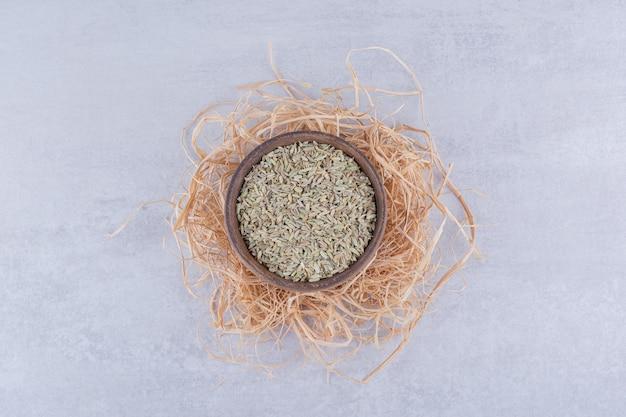 Grüne trockene anissamen in einer platte auf konkretem hintergrund. foto in hoher qualität