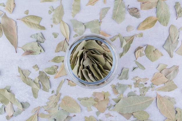 Grüne trockene lorbeerblätter in einem becherbehälter