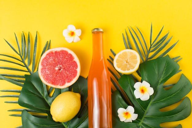 Grüne tropische pflanzenblätter und flasche getränk