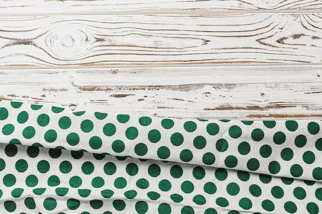 Grüne tupfenserviette auf verwitterter holzoberfläche