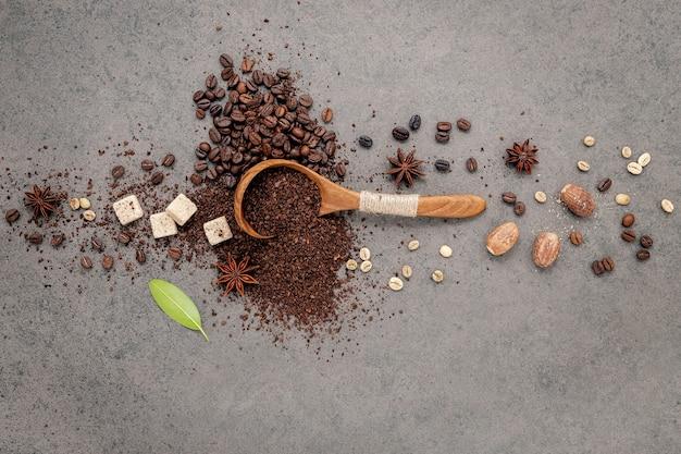 Grüne und braune ungeröstete und dunkel geröstete kaffeebohnen in einer holzschale mit löffeln auf dunklem beton.