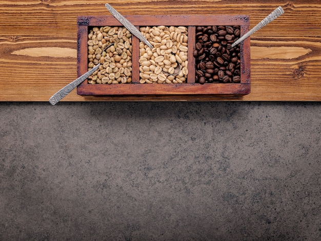Grüne und braune ungeröstete und dunkel geröstete kaffeebohnen in holzkiste mit löffeln auf dunklem beton.