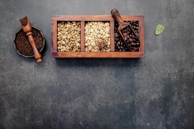 Grüne und braune ungeröstete und dunkel geröstete kaffeebohnen in holzkiste mit schaufeln auf dunklem beton.