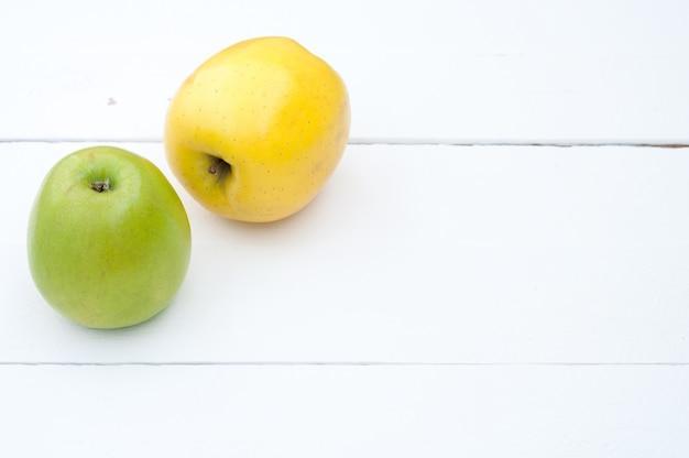 Grüne und gelbe äpfel auf einer weißen hölzernen hintergrundnahaufnahme