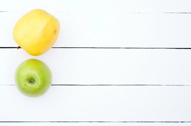 Grüne und gelbe äpfel auf einer weißen hölzernen hintergrundoberansicht
