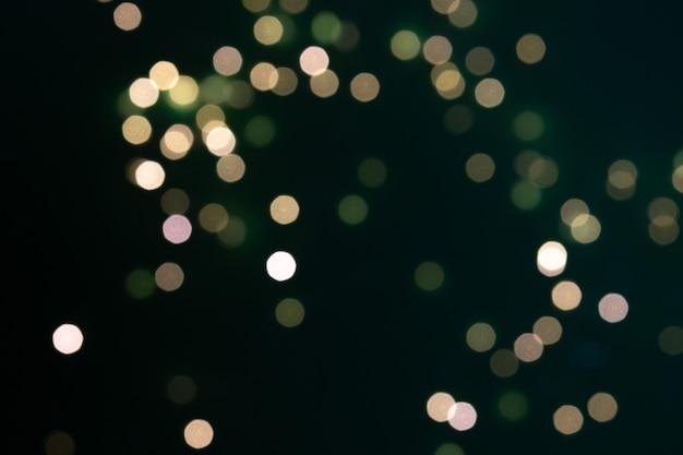 Grüne und gelbe bokeh-lichter auf schwarzem hintergrund