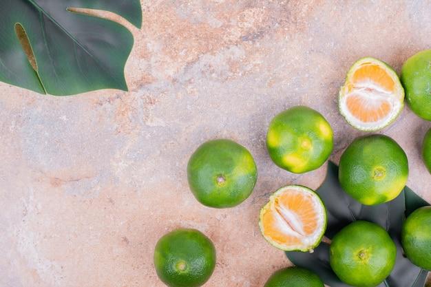 Grüne und gelbe mandarinen auf rosa tisch.