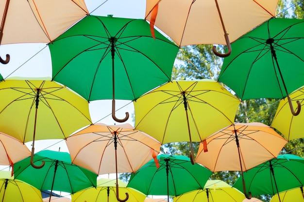 Grüne und gelbe regenschirme hängen über den straßen der stadt. bunte regenschirme im himmel.