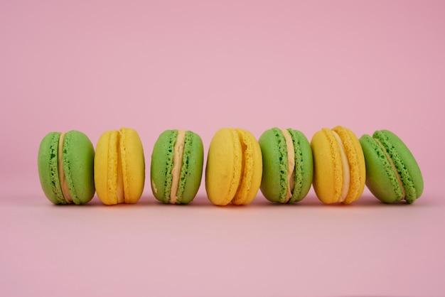 Grüne und gelbe runde gebackene macarons auf einem rosa hintergrund