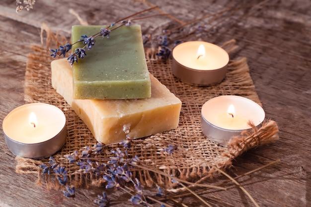 Grüne und gelbe seifen mit einer duftkerze in einer romantischen umgebung auf holzoberfläche.