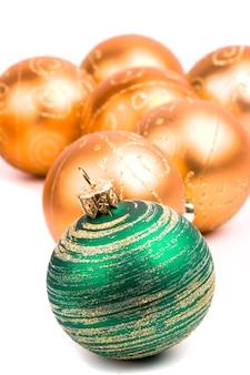 Grüne und goldene glasweihnachtsballnahaufnahme auf weißem hintergrund
