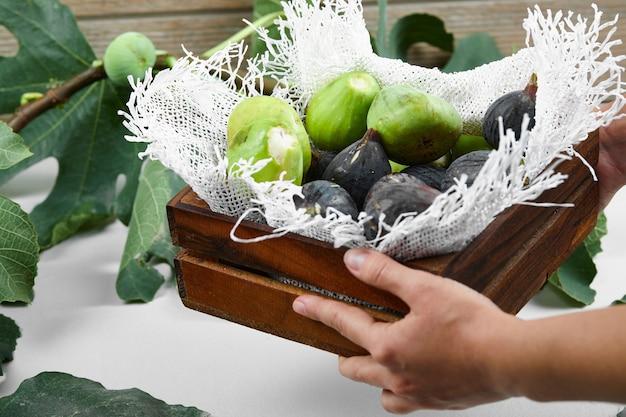 Grüne und lila feigen in einem tablett auf einem stück sackleinen.