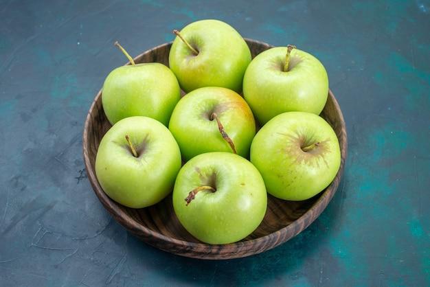 Grüne und milde grüne äpfel der vorderansicht auf dem dunkelblauen schreibtischfrucht-pflanzenbaum der frischen pflanze