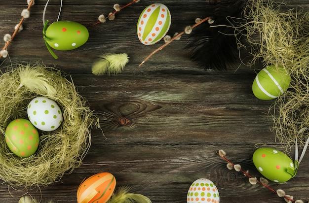Grüne und orange ostereier in einem sisalnest auf einem alten hölzernen hintergrund. vogelfedern. bemalte eier
