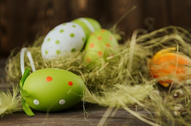 Grüne und orange ostereier in einem sisalnest auf einem hölzernen oberflächenkopierraum. bemalte eier. vogelfedern