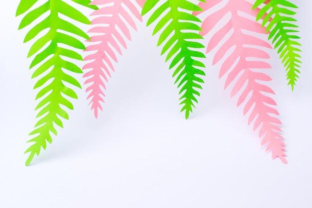 Grüne und rosa tropische papierpalmenblätter auf weißer oberfläche
