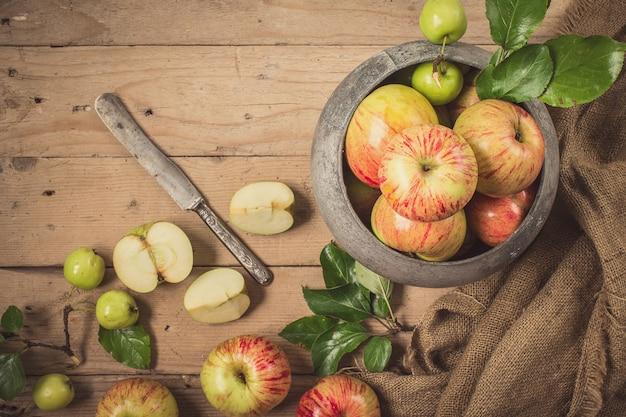 Grüne und rote äpfel auf rustikaler tabelle. flach liegen