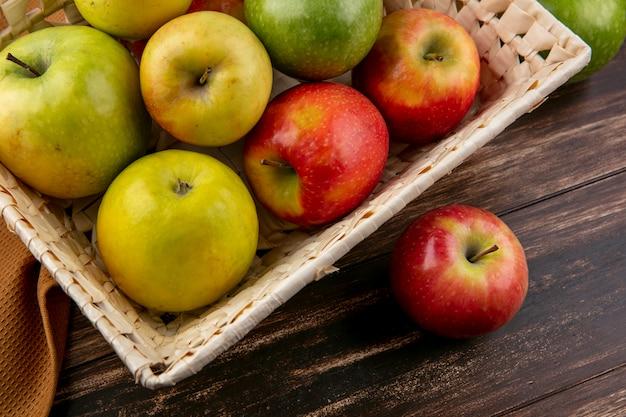Grüne und rote äpfel der seitenansicht in einem korb auf einem braunen handtuch auf einem hölzernen hintergrund