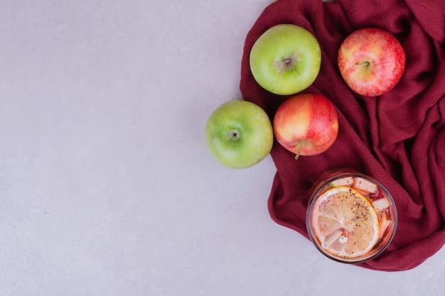 Grüne und rote äpfel mit einem glas saft in samtiger tischdecke.