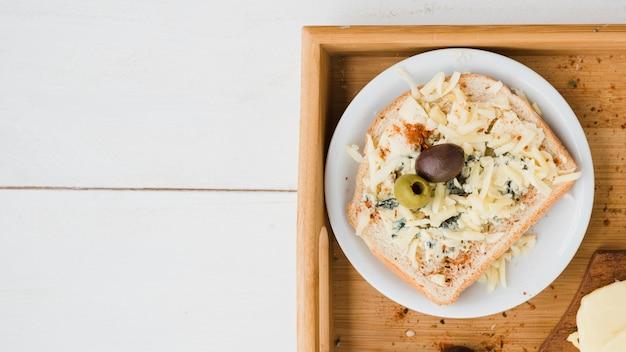 Grüne und rote oliven mit geriebenem käse auf brot über der platte im behälter
