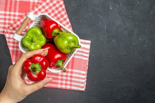 Grüne und rote paprika der draufsicht im plastikkorb auf roter weißer karierter tischdecke roter paprika in der weiblichen hand auf freiem raum der dunklen oberfläche