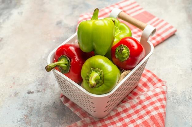 Grüne und rote paprika der draufsicht in der rotweißen karierten tischdecke des plastikkorbs auf der nackten oberfläche