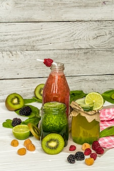 Grüne und rote smoothies in einem glas mit limette, kiwi