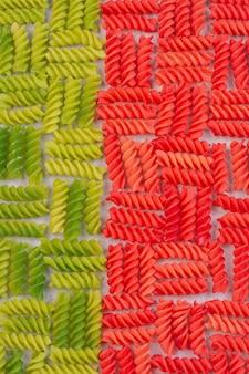 Grüne und rote ungekochte makkaroni auf weißer oberfläche