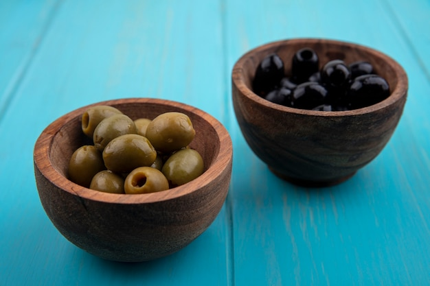 Grüne und schwarze oliven der vorderansicht in schalen auf türkisfarbenem hintergrund