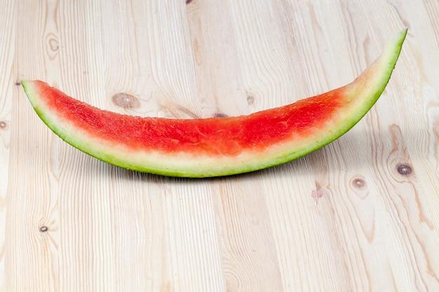Grüne ungenießbare kruste mit geschnittenem rotem und saftigem fruchtfleisch der wassermelone