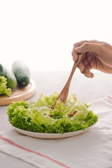 Grüne vegane frühstücksmahlzeit in schüssel mit salat, gurke, limette und mandel. mädchen hält platte mit den händen sichtbar, ansicht von oben. sauberes essen, diät, veganes lebensmittelkonzept