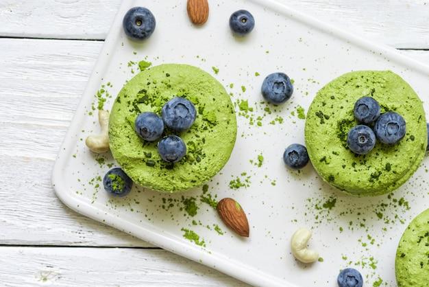 Grüne vegane matcha-rohkuchen mit blaubeeren, minze und nüssen. gesundes leckeres essen