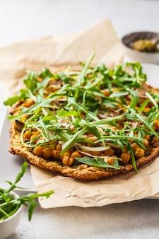 Grüne vegane pizza mit pesto, kichererbsen, champignons und rucola.