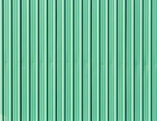 Grüne verzinkte stahlplatte als zaunwand, nahtloses abstraktes hintergrundgrün mit vertikalen linien