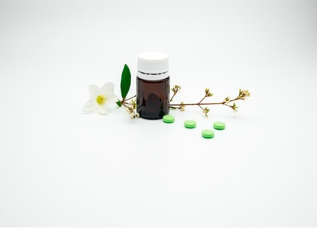 Grüne vitamin- und ergänzungstablettenpillen mit blume und niederlassung und leere aufkleberbernsteinfarbige glasflasche auf weißem hintergrund mit kopienraum, addieren gerade ihren eigenen text