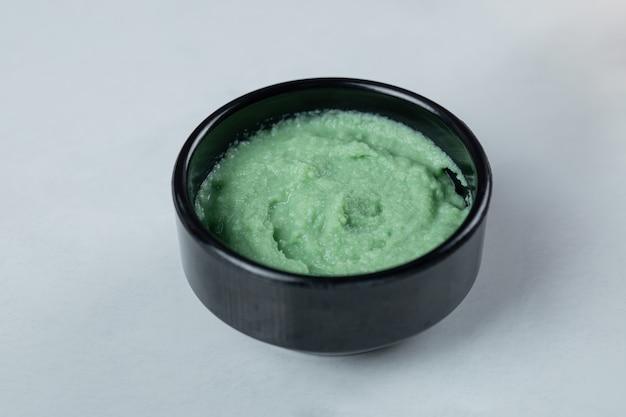 Grüne wasabi-sauce in einer schwarzen untertasse.