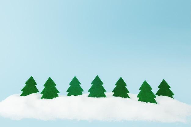 Grüne weihnachtsbäume auf blauem hintergrund mit kunstschnee. foto in hoher qualität
